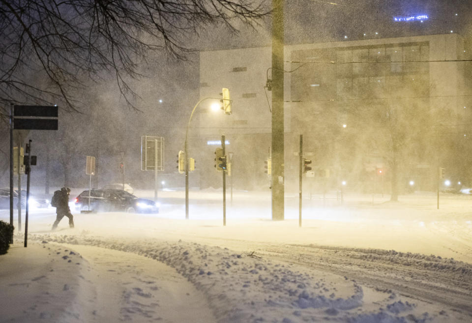 A man walks across a snow-covered road in the early morning with snowdrifts in Bielefeld, Germany, Sunday, Feb. 7, 2021. (Marcel Kusch/dpa via AP)