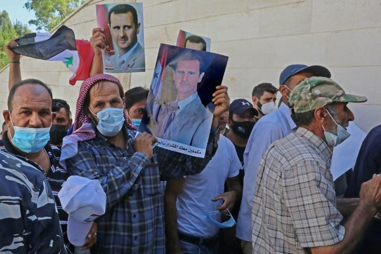 Syrian residents of Lebanon hold portraits of Bashar al-Assad, as they queue outside the embassy to cast early ballots for next Wednesday's presidential election which is expected to give the veteran incumbent a new term