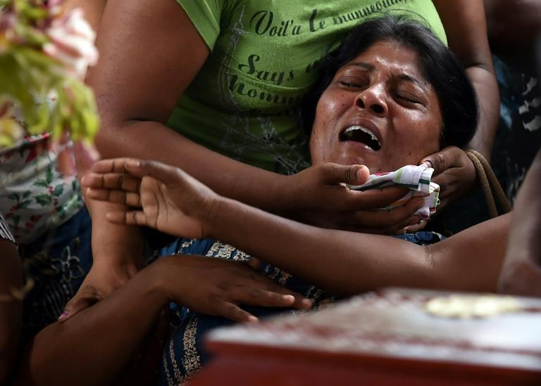 A Sri Lankan woman grieves at the coffin of her daughter who died when a garbage dump collapsed in Colombo