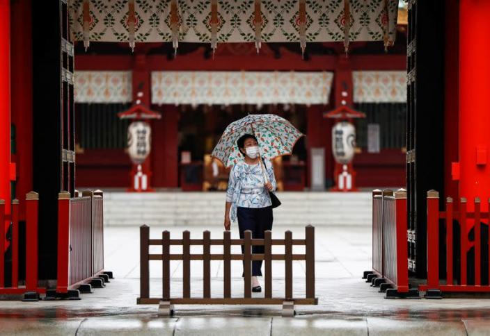 A woman wearing a protective face mask walks amid the coronavirus disease (COVID-19) outbreak, in Tokyo
