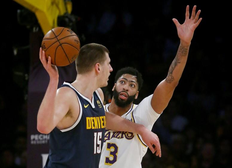 LOS ANGELES, CALIF. - DEC. 22, 2019. Lakers forward Anthony Davis defends against Nuggets center Nikola Jokic in the first quarter Sunday night, Dec. 22, 2019, at Staples Center in Los Angeles (Luis Sinco/Los Angeles Times)