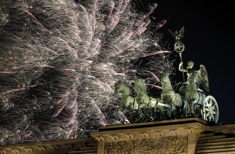 Fireworks light the sky above the Quadriga at the Brandenburg Gate shortly after midnight in Berlin, Germany, Tuesday, Jan. 1, 2019. Hundred thousands of people celebrated New Year's Eve welcoming the new year 2019 in Germany's capital