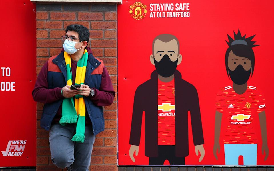 A Manchester United fan is seen wearing a face mask - Getty