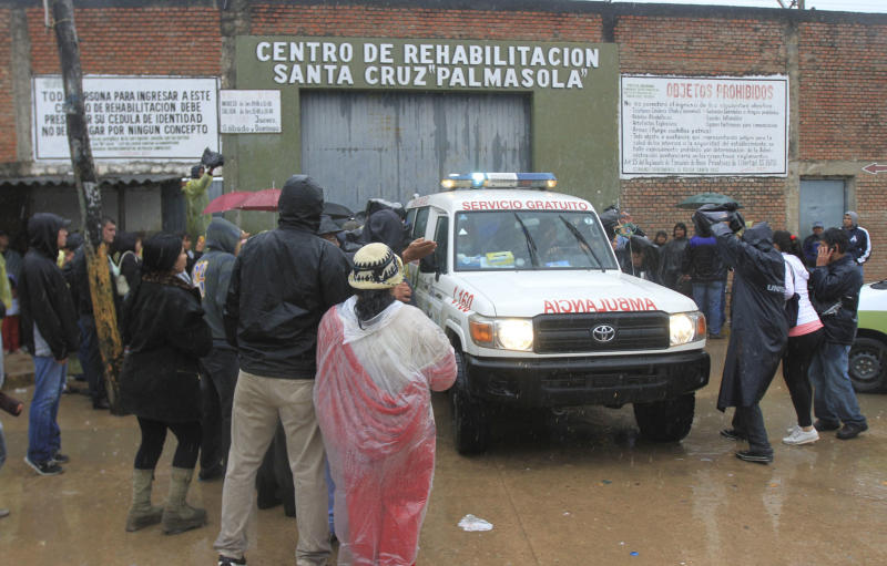 Inmates relatives and members of the press surround an ambulance leaving the Palmasola jail in Santa Cruz, Bolivia, Friday, Aug. 23, 2013. At least 15 inmates were killed, many in a fire, early Friday in a battle among inmates for control of part of an overcrowded maximum-security prison in Bolivia's eastern lowlands, according to National Police Chief Alberto Aracena. (AP Photo)