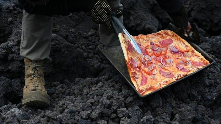 David Garcia checks a pizza he is cooking on the lava rivers that come down from the Pacaya volcano, May 2021