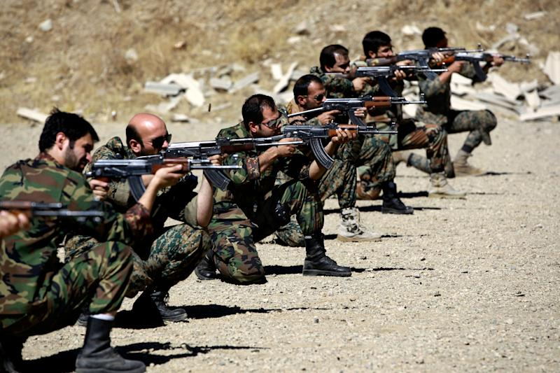 In this Thursday, Sept. 19, 2013 photo, members of the Basij paramilitary militia fire their weapons during a training session, in Tehran, Iran. The Basij has its roots as volunteer fighters during the 1980-88 war with Iraq. It then developed as a grass-roots defender of the system _ taking on roles such as Islamic morality police at checkpoints and parks or as shock troops busting up pro-reform gatherings or publications. Precise numbers on Basij membership are not published, but some estimates range as high as 1 million or more. (AP Photo/Ebrahim Noroozi)