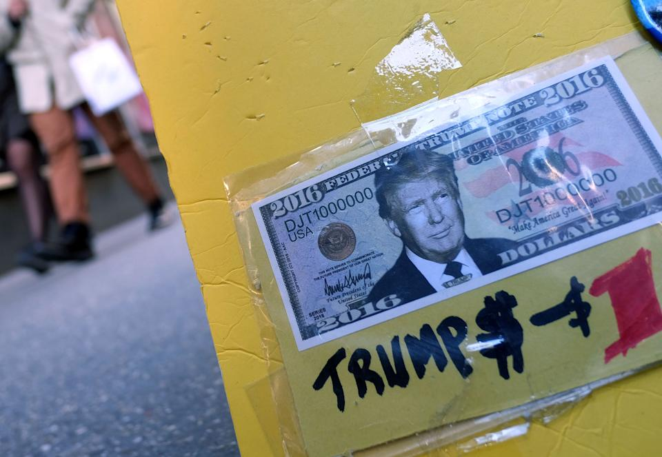 A fake dollar bill with US Republican presidential candidate Donald Trump's picture on it is displayed for sale with other electoral items at a roadside stall as pedestrians walk past in New York on February 26, 2016. White House hopefuls Ted Cruz and Marco Rubio unleashed a barrage of attacks against Donald Trump during raucous Republican debate on February 25, as they sought to halt the billionaire frontrunner's seemingly relentless march to the party's nomination. / AFP / Jewel Samad        (Photo credit should read JEWEL SAMAD/AFP/Getty Images)