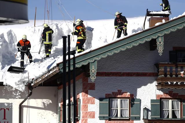Firefighters clear the snow from a roof in Inzell, Germany, Wednesday, Jan. 16, 2019. (AP Photo/Matthias Schrader)