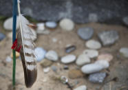 In this May 1, 2019 photo, a feather and stones are left at the Charles Shay Memorial at Omaha Beach in Saint-Laurent-sur-Mer, Normandy, France. Shay, was a medic who on June 6, 1944, landed on Omaha Beach, where he helped drag wounded soldiers out of the rising tide, saving them from drowning. (AP Photo/Virginia Mayo)