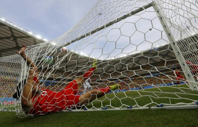 Switzerland's Ricardo Rodriguez falls into the goal net after making a save during their 2014 World Cup Group E soccer match against Honduras at the Amazonia arena in Manaus June 25, 2014. REUTERS/Michael Dalder (BRAZIL - Tags: SOCCER SPORT WORLD CUP TPX IMAGES OF THE DAY) TOPCUP