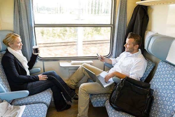 Man and woman sitting in train talking smiling commuters friends
