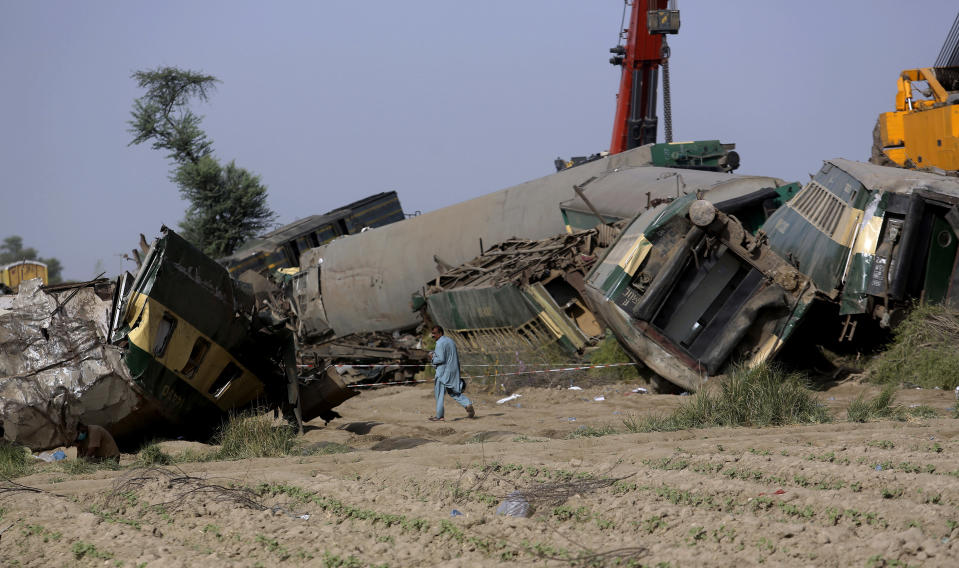 A railway worker walks past the wreckage at the site of a train collision in the Ghotki district, southern Pakistan, Tuesday, June 8, 2021. The death toll from a deadly train accident in southern Pakistan jumped to dozens on Tuesday after rescuers pulled a dozen more bodies from crumpled cars of two trains that collided on a dilapidated railway track a day ago, an official said, as rescue work continued even 24 hours after the incident to find any survivors. (AP Photo/Fareed Khan)