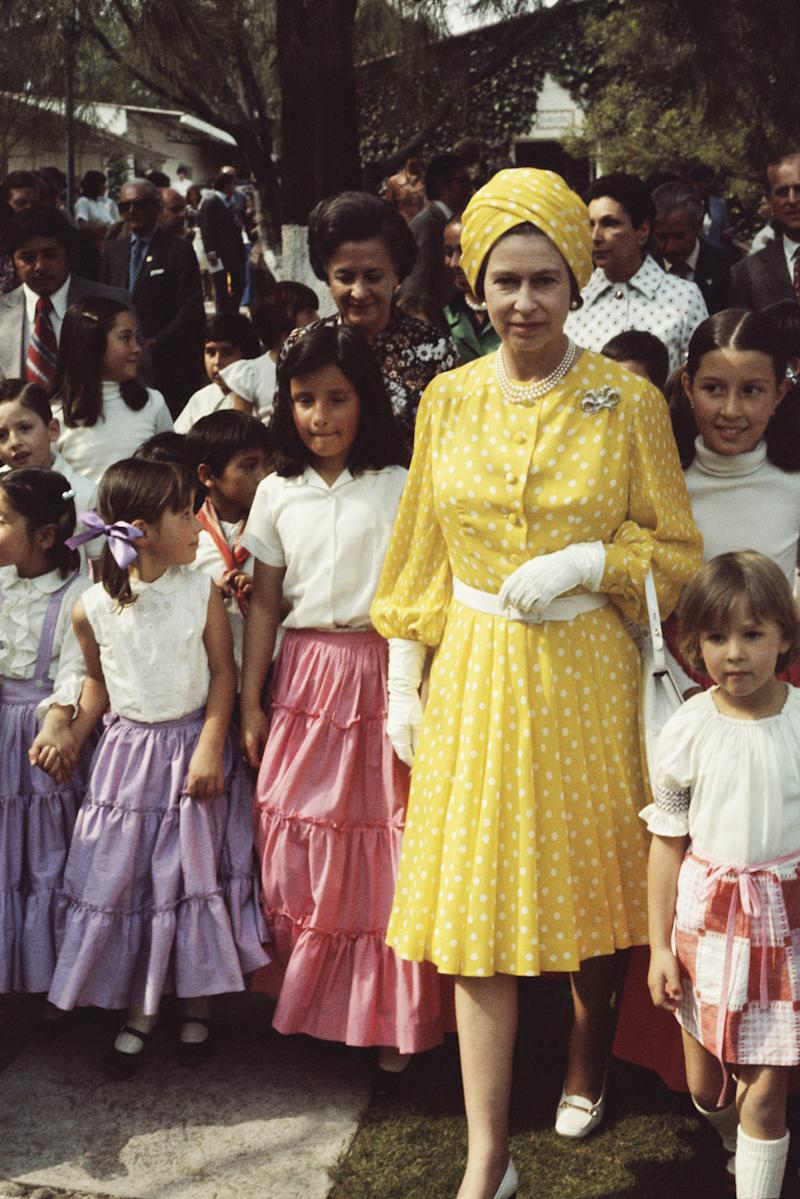 Queen Elizabeth II with a group of local children during her state visit to Mexico, 1975. Photo by Serge Lemoine/Getty Images.