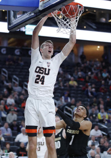 Oregon State's Kylor Kelley dunks over Colorado's Tyler Bey during the second half of an NCAA college basketball game in the quarterfinals of the Pac-12 men's tournament Thursday, March 14, 2019, in Las Vegas. (AP Photo/John Locher)