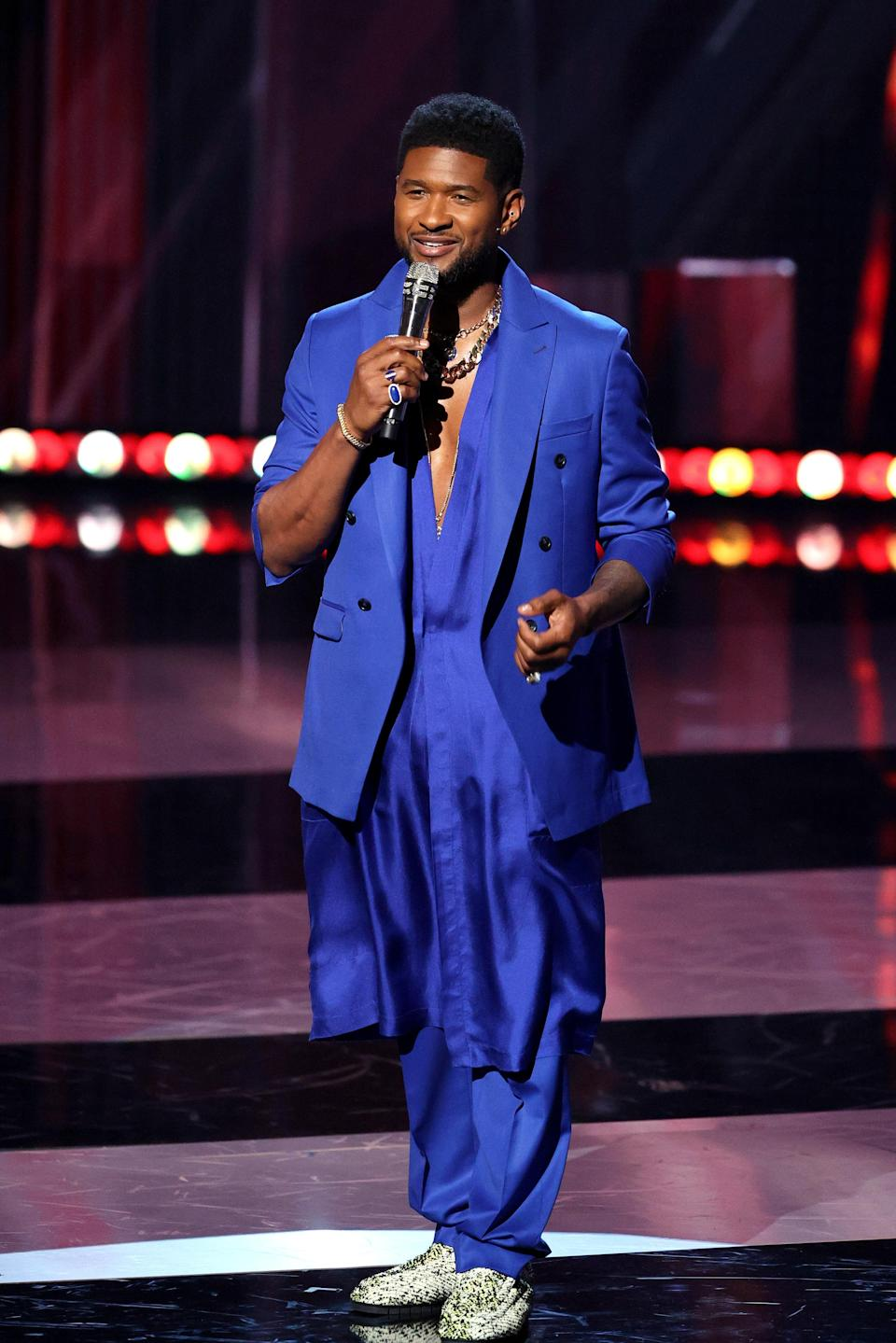 One of his many outfit changes featured an entirely electric blue look with a chunky gold chain and a bare chest. A look that's proving to be pretty popular!