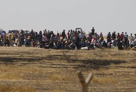 Syrian refugees wait near the border fences as they are pictured from the Turkish side of the border, near Akcakale in Sanliurfa province, Turkey, June 11, 2015. REUTERS/Osman Orsal