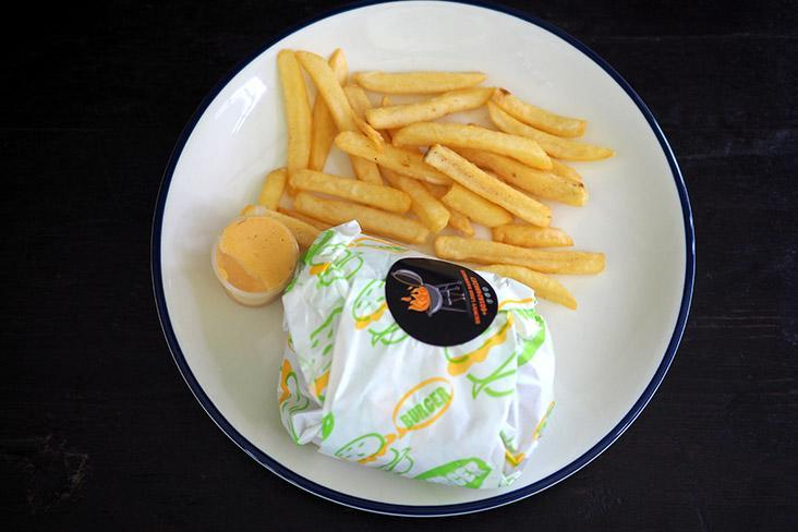 The burger is wrapped in paper and served with fries and a mild chilli mayonnaise sauce