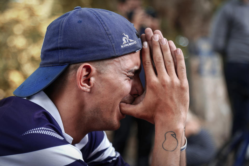 A soccer fan mourns the death of Diego Maradona outside the stadium of the soccer club Gimnasia y Esgrima, coached by Maradona, in La Plata, Argentina, Wednesday, Nov. 25, 2020. The Argentine soccer great who was among the best players ever and who led his country to the 1986 World Cup title before later struggling with cocaine use and obesity, died from a heart attack on Wednesday at his home in Buenos Aires. He was 60. (AP Photo/Maria Paula Avila)