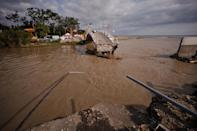 A bridge is destroyed by flooding in the Black Sea resort of Gelendzhik, southern Russia, Saturday, July 7, 2012. Torrential rains dropped nearly a foot of water in the Black Sea region of southern Russia overnight, unleashing intense flooding that killed over a hundred people and forced many to scramble out of their beds for refuge in trees and on roofs, officials said Saturday. (AP Photo/Ignat Kozlov)