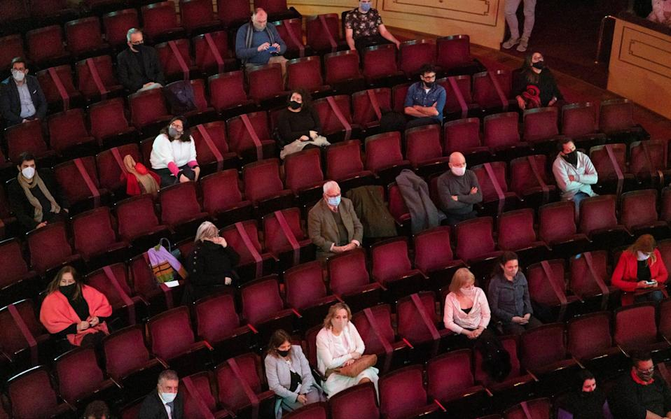 People wearing face masks and keeping a safe distance from each other in a theatre in Uruguay, as Boris Johnson eases more lockdown restrictions in the UK to allow theatres to reopen from August 15 - AP Photo/Matilde Campodonico