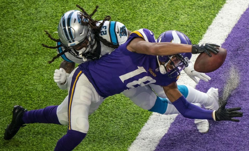 Minnesota Vikings wide receiver Justin Jefferson (18) dives past Carolina Panthers cornerback Stantley Thomas-Oliver (23) to score his second touchdown of the day in the fourth quarter of an NFL football game in Minneapolis, Sunday, Nov. 29, 2020. (Alex Kormann/Star Tribune via AP)