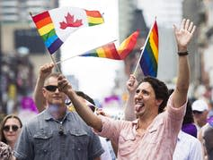 Justin Trudeau laughs and sticks out his tongue while waving a Pride flag.