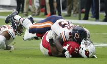 <p>Chicago Bears linebacker Danny Trevathan, top, tackles Arizona Cardinals running back David Johnson (31) for a loss as Bears defensive end Roy Robertson-Harris, left, looks on during the first half of an NFL football game, Sunday, Sept. 23, 2018, in Glendale, Ariz. (AP Photo/Rick Scuteri) </p>