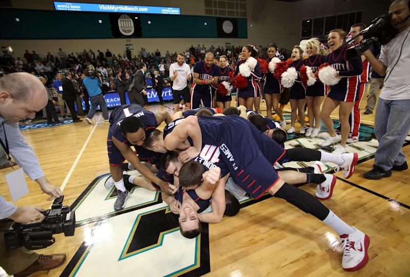 Liberty players celebrate at mid-court after defeating Charleston Southern 87-76 in an NCAA college basketball game in the championship at the Big South Conference tournament on Sunday March 10, 2013 in Conway, S.C. (AP Photo/Willis Glassgow