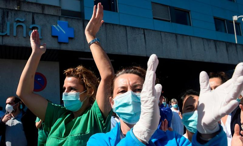 Healthcare workers dealing with the coronavirus crisis in A Coruña applaud in return as they are cheered on outside the city's university hospital