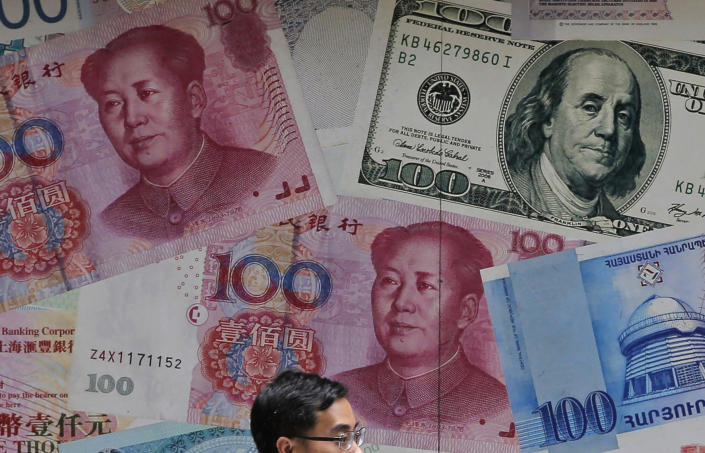 FILE - In this June 10, 2019, file photo, a man walks past a money exchange shop decorated with different banknotes at Central, a business district of Hong Kong. The U.S. Treasury Department labeled China a currency manipulator Monday, Aug. 5, after Beijing pushed down the value of its yuan in a dramatic escalation of the trade conflict between the world's two biggest economies. (AP Photo/Kin Cheung, File)