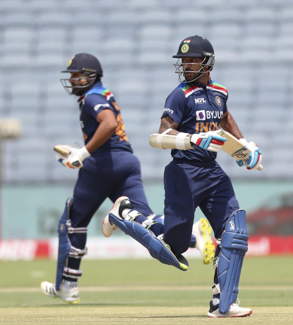 Indian cricketers Shikhar Dhawan, right, and Rohit Sharma run between the wickets during the second one-day international cricket match between India and England in Pune, India, Friday, March 26, 2021. (AP Photo/Rafiq Maqbool)