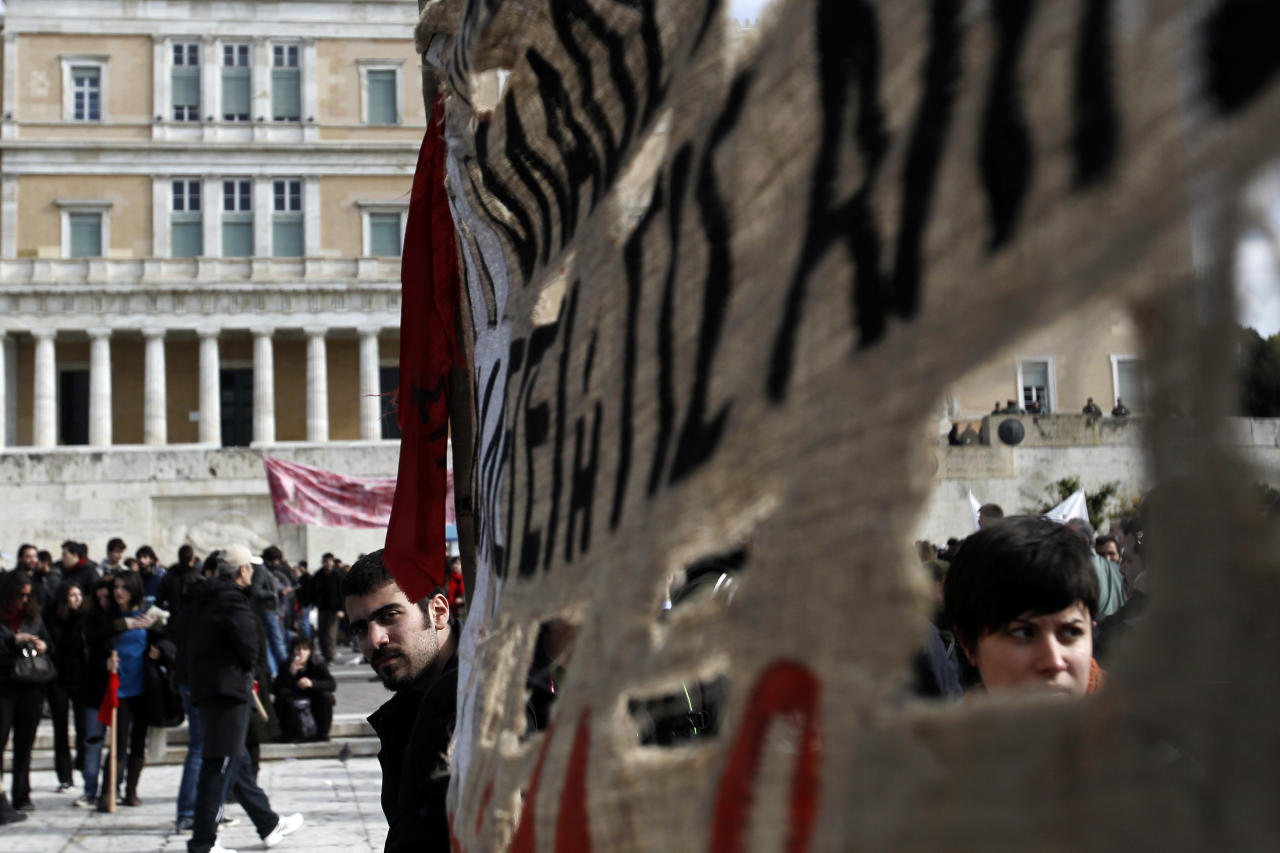 Protesters carry a banner during a rally outside the Greek Parliament in Athens, Saturday, Feb. 11, 2012. The leaders of the two parties backing Greece's coalition government called on their deputies Saturday to back legislation that calls for harsh new austerity measures, essential if Greece is to get a new bailout deal and stave off bankruptcy. (AP Photo/Petros Giannakouris)
