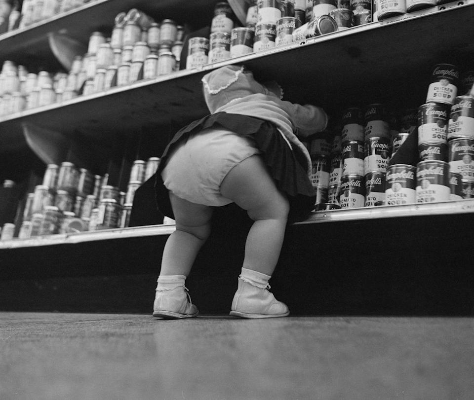 """<p>A curious toddler reaches for the stacked selection of Campbell's Tomato Soup.</p><p>The iconic brand <a href=""""https://www.campbellsoup.co.uk/blog/campbells-soup-history-condensed-version/"""" rel=""""nofollow noopener"""" target=""""_blank"""" data-ylk=""""slk:began in 1869"""" class=""""link rapid-noclick-resp"""">began in 1869</a> and was founded by Joseph A. Campbell, a fruit merchant and Abraham Anderson, an icebox manufacturer.</p>"""