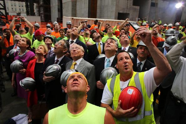 With developer Larry Silverstein (yellow tie) behind him, construction worker Frank Gasior (C) watches as the last steel beam, signed by members of the crews that helped build the tower, is hoisted 977 feet to the top of Four World Trade Center on June 25, 2012 in New York City. The trapezoidal glass and steel office building, which is designed as an architectural backdrop to the September 11 Memorial, is scheduled to open in 2013. (Photo by Spencer Platt/Getty Images)