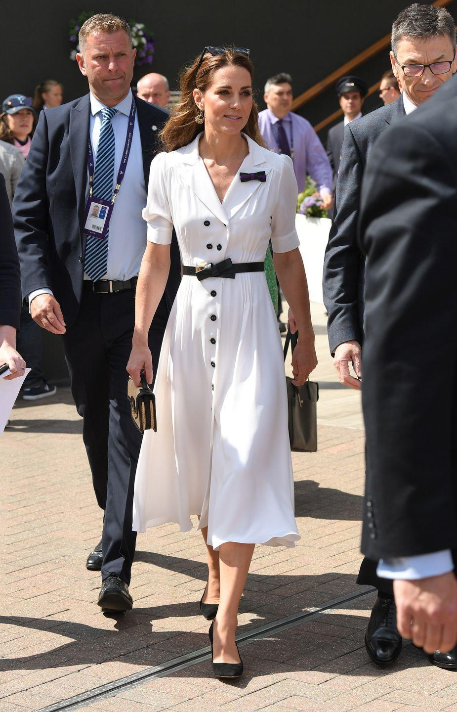 <p>The Duchess of Cambridge wore a white midi dress by Suzannah which she paired with a belt and an Alexander McQueen bag for the tennis competition.</p>