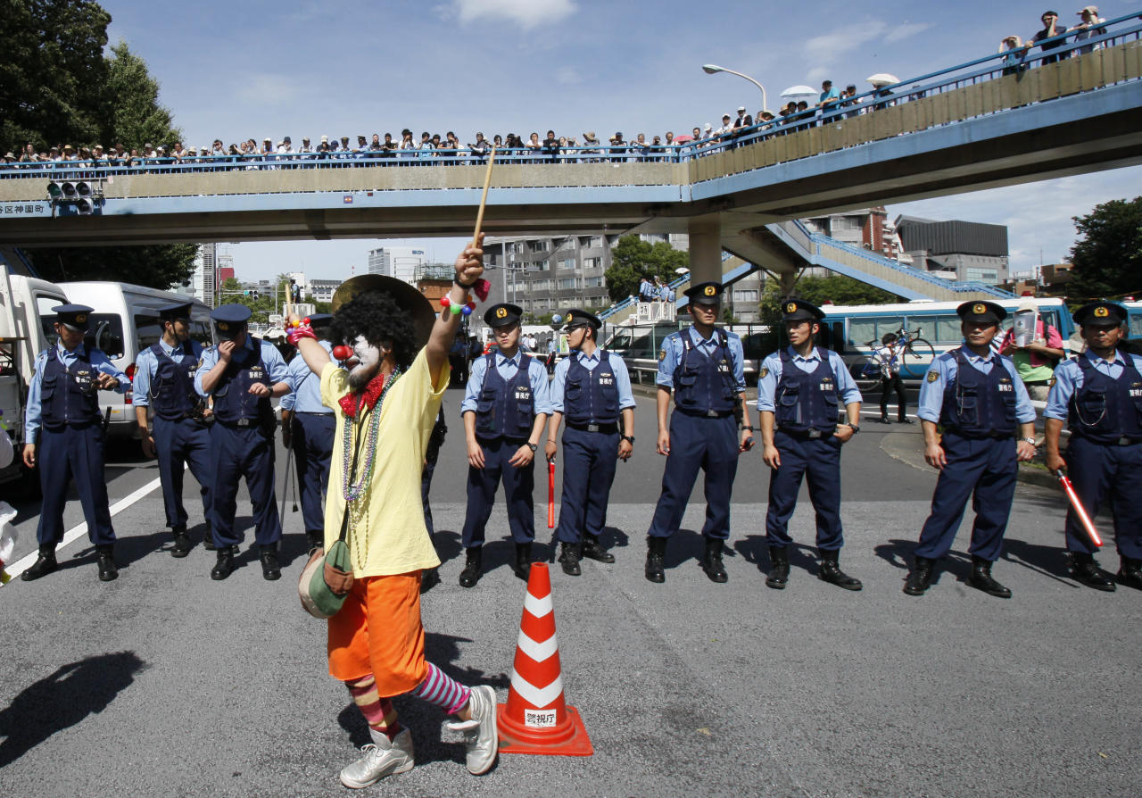 "An anti-nuclear protester dressed as a clown is watched by police officers during a rally in downtown Tokyo Monday, July 16, 2012. Tens of thousands of people gathered at a Tokyo park, demanding ""Sayonara,"" or goodbye, to nuclear power as Japan prepares to restart yet another reactor, and expressed outrage over a report that blamed culture on the Fukushima disaster. (AP Photo/Koji Sasahara)"