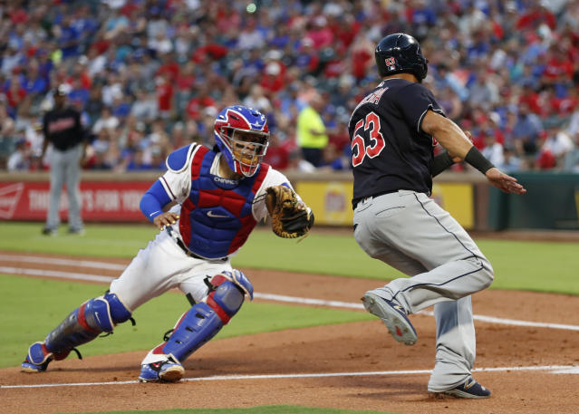 Cleveland Indians' Melky Cabrera (53) avoids a tag by Texas Rangers catcher Robinson Chirinos, left, to score on a single hit by teammate Yan Gomes during the fifth inning of a baseball game, Saturday, July 21, 2018, in Arlington, Texas. (AP Photo/Jim Cowsert)