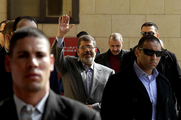 """FILE - In this Friday, Jan. 4, 2013 file photo, Egyptian President Mohammed Morsi, center, waves to supporters after attending Friday prayers at the Hassan Sharbatli mosque on the outskirts of Cairo, Egypt. Morsi, in a rambling 2.15-hour TV interview that aired in the early hours of Monday, Feb, 25, 2013, dismissed the masses protesting against his rule across much of the nation as """"thugs"""" and """"outlaws."""" (AP Photo/Ahmed Abd El Latif, Shorouk newspaper, File) EGYPT OUT"""