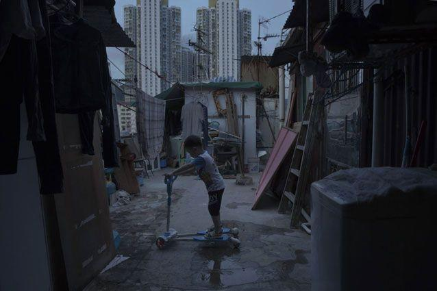 A five-year-old boy plays outside his tiny home which is made of concrete and corrugated metal on the terrace of a apartment block. Photo: AP