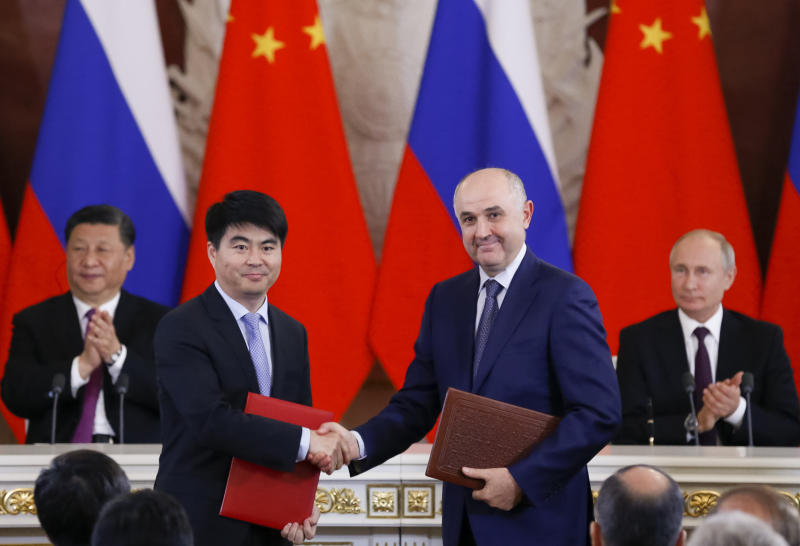 Guo Ping, deputy Chairman of Huawei Technologies Co Ltd, foreground left, shakes hands with Russian President of MTS mobile network operator, Alexei Kornya as Russian President Vladimir Putin, right, and Chinese President Xi Jinping attend a signing ceremony following their talks in the Kremlin in Moscow, Russia, Wednesday, June 5, 2019. Chinese President Xi Jinping is on visit to Russia this week and is expected to attend Russia's main economic conference in St. Petersburg. (AP Photo/Alexander Zemlianichenko, Pool)
