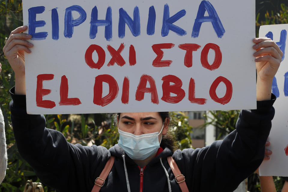 """A protestor holds a banner reading in Greek """" Peace, not to the El Diablo"""" , outside Cyprus' national broadcasting building, during a protest, in capital Nicosia, Cyprus, Saturday, March 6, 2021. The Orthodox Church of Cyprus is calling for the withdrawal of the country's controversial entry into this year's Eurovision song context titled """"El Diablo"""", charging that the song makes an international mockery of country's moral foundations by advocating """"our surrender to the devil and promoting his worship."""" (AP Photo/Petros Karadjias)"""
