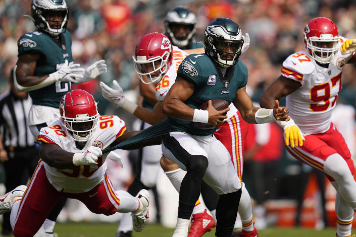 Philadelphia Eagles quarterback Jalen Hurts (1) runs with the ball as Kansas City Chiefs defensive tackle Jarran Reed (90) holds on to part of Hurts' uniform during the first half of an NFL football game Sunday, Oct. 3, 2021, in Philadelphia. (AP Photo/Matt Slocum)
