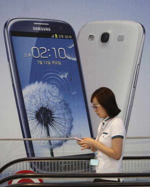 A woman walks by a sign advertising Samsung's mobile phone Galaxy III at the showroom of its headquarters in Seoul, South Korea, Friday, Aug. 24, 2012. The Seoul Central District Court ruled Friday that technology rivals Apple Inc. and Samsung Electronics Co. both infringed on each other's patents, and ordered a partial ban of their products in South Korea. Each side was also ordered to pay limited damages. The court ordered Apple to remove the iPhone 3GS, iPhone 4, iPad 1 and iPad 2 from store shelves in South Korea, ruling that the products infringed on two of Samsung's telecommunications patents. (AP Photo/Ahn Young-joon)