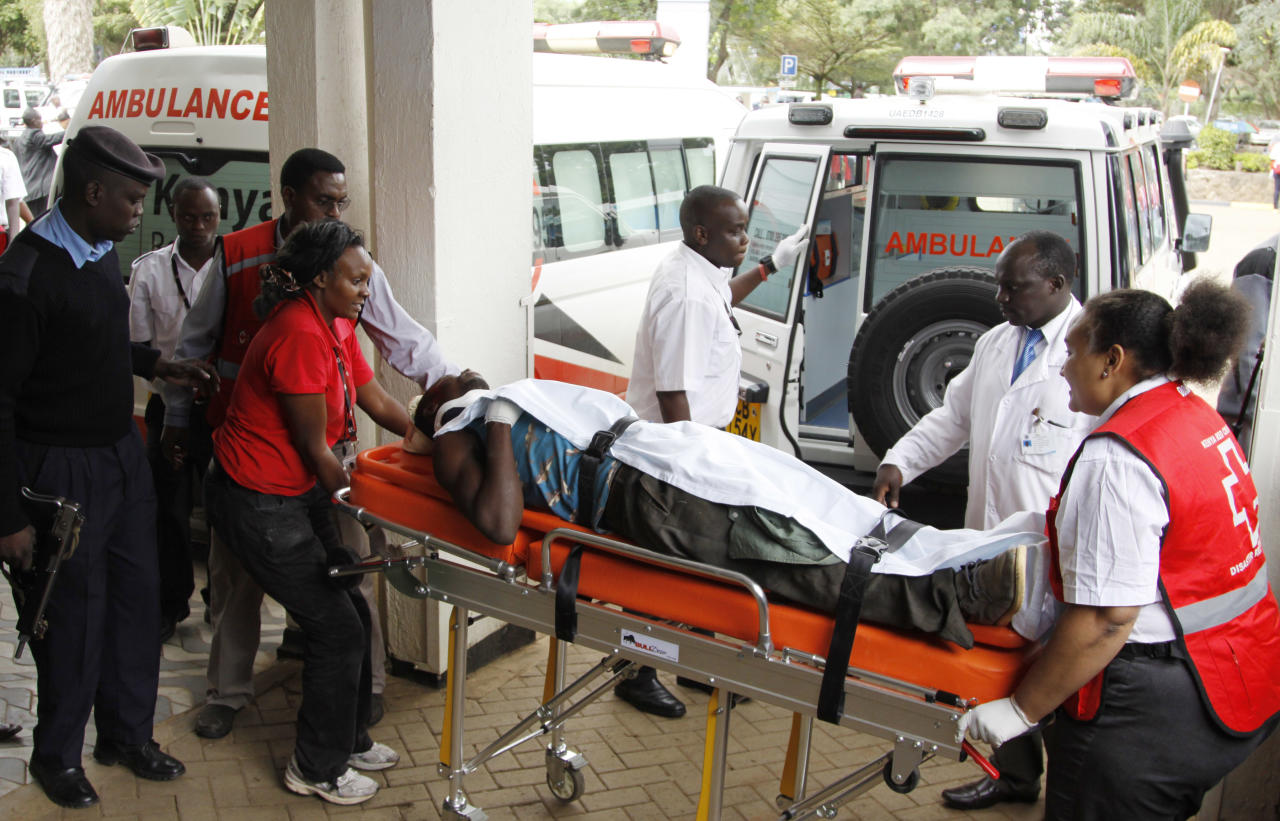 Doctors and medical staff help a man injured in the Mander attack, as he arrives to be treated at Kenyatta National Hospital in Nairobi, Kenya ,Tuesday July 7, 2015. At least 14 people were killed in an attack early Tuesday in the country's north by al-Shabab, Islamic extremist rebels from neighboring Somalia, a Kenyan official said. Eleven people were also wounded in the attack which took place in Soko Mbuzi village in Mandera County near Kenya's border with Somalia, said Mandera County Commissioner Alex Nkoyo. (AP Photo/ Khalil Senosi)