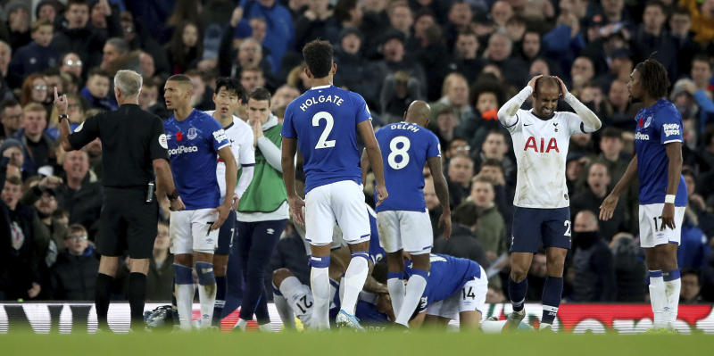 Everton players check on the condition of team-mate Andre Gomes following a challenge by Tottenham Hotspur's Son Heung-min, second left, during the English Premier League soccer match at Goodison Park, Liverpool, England, Sunday Nov. 3, 2019. (Nick Potts/PA via AP)