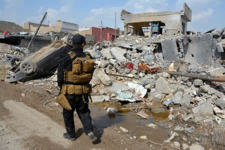 A member of the Counter Terrorism Service (CTS) walks at the site after an air strike attack against Islamic State triggered a massive explosion in Mosul