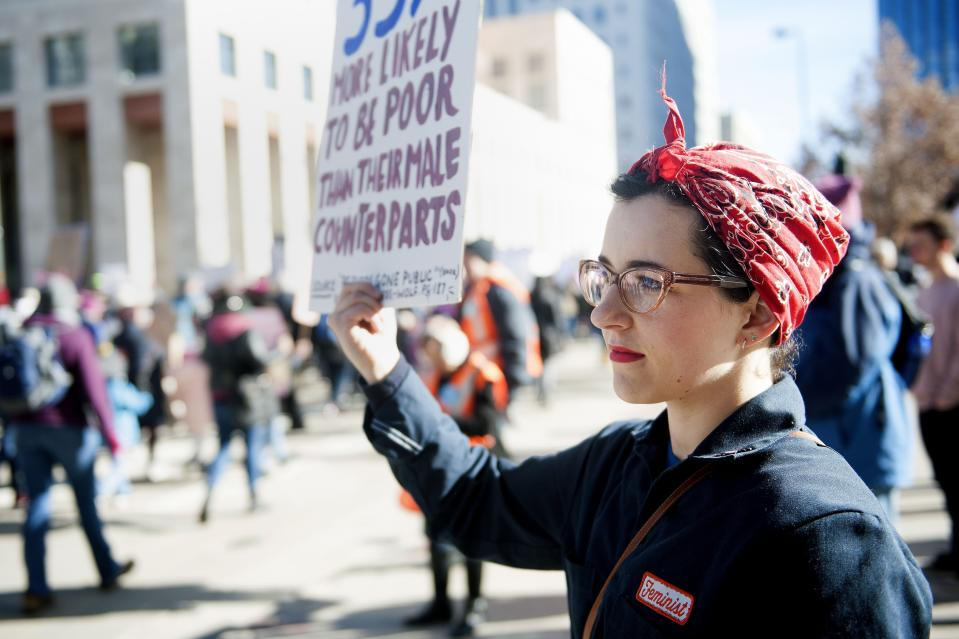 Lily Williams of Denver, Colorado dressed as Rosie the Riveter, holds up a sign as demonstrators march past her during during the Women's March in Denver, Colorado on January 19, 2019. - Thousands of women gathered across the United States for their annual message opposing Donald Trump and supporting women's rights. (Photo by Jason Connolly / AFP)        (Photo credit should read JASON CONNOLLY/AFP via Getty Images)