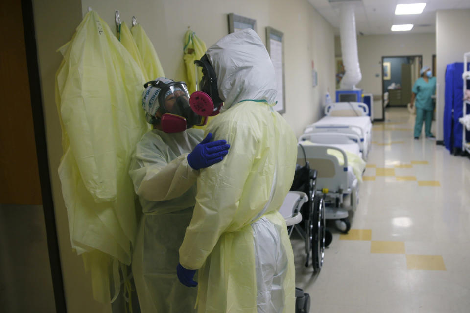 Medical personnel talk as they care for COVID-19 patients at DHR Health, Wednesday, July 29, 2020, in McAllen, Texas. (AP Photo/Eric Gay)