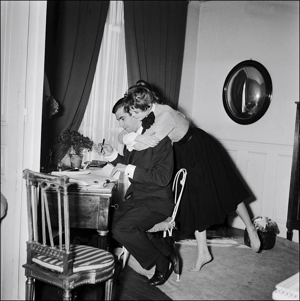 <p>Brigitte Bardot wraps her arms around her husband, French director Roger Vadim, while he works at their Parisian pad. </p>