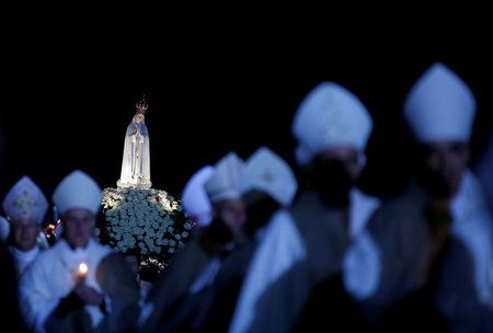 FILE PHOTO: A statue of the Holy Virgin Mary of Fatima is carried during a candlelight vigil, as pilgrims attend the 99th anniversary of the appearance of the Virgin Mary to three shepherd children, at the Catholic shrine of Fatima, Portugal, May 12, 2016. REUTERS/Rafael Marchante/File Photo